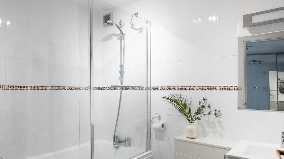 The family bathroom has a well-sized bath with a mains shower above, the washbasin has an illuminated mirror above.