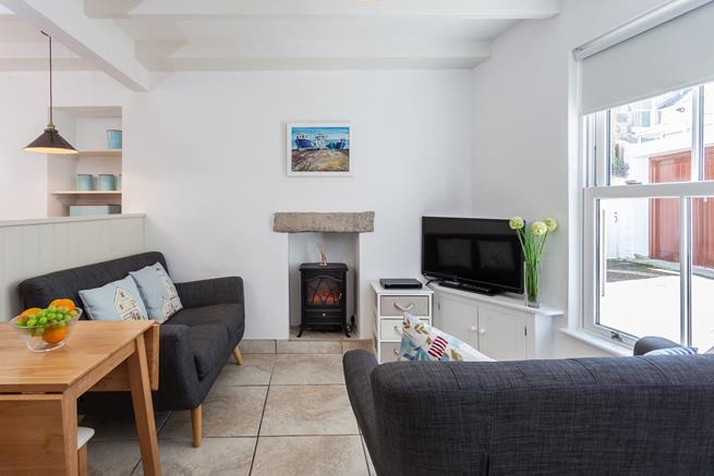 Open plan living area with electric woodburner effect fire.