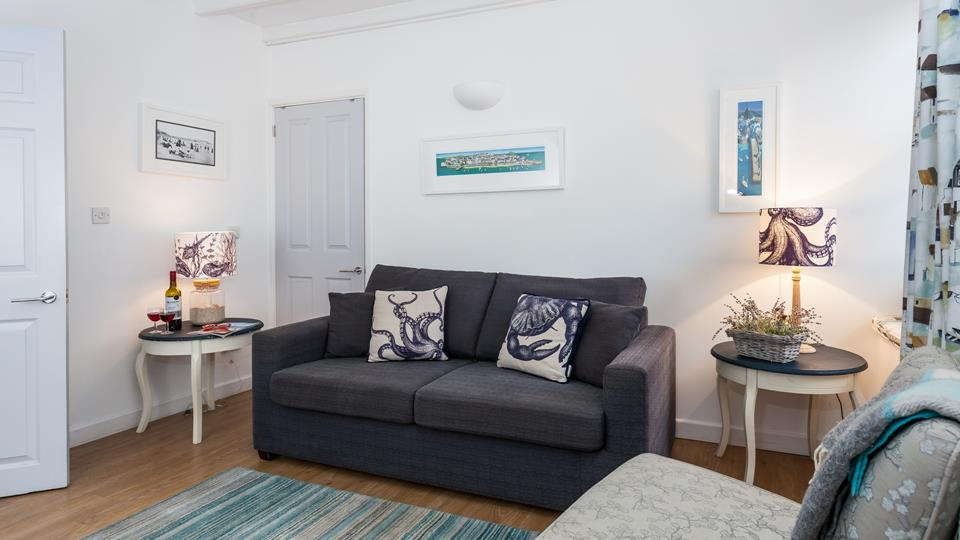 The living room is bright and airy with stunning nautical art that nods to St Ive's rich artistic history.