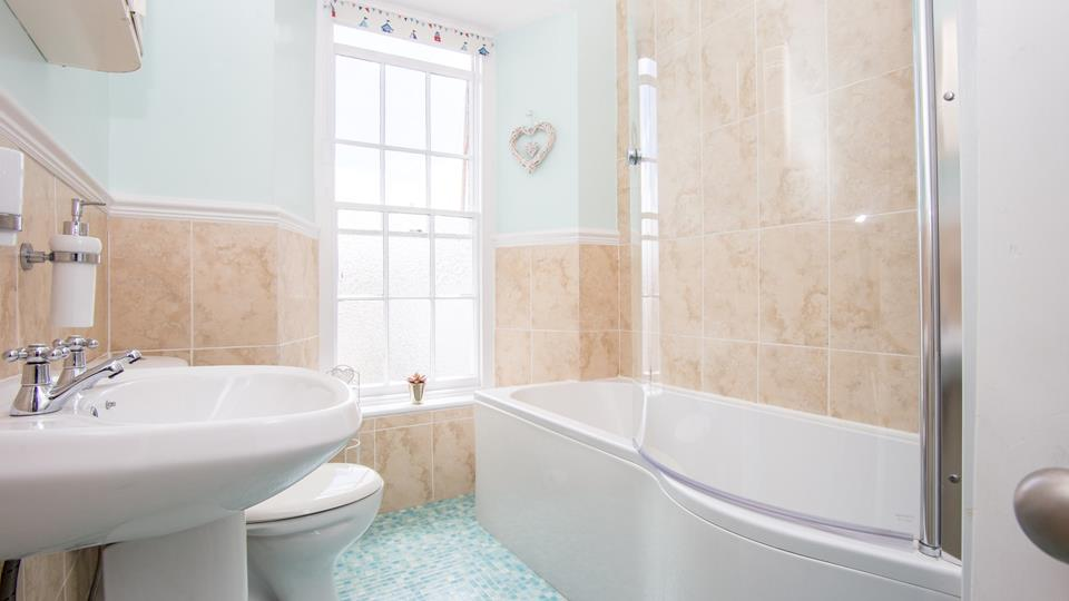 Treat yourself to a relaxing bubble bath in the spacious coastal themed bathroom.