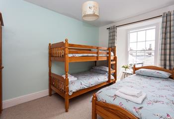 Triple bedroom in pastel shades.