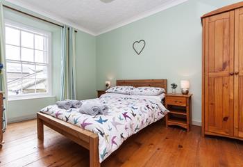 Double bedroom with wooden floor.