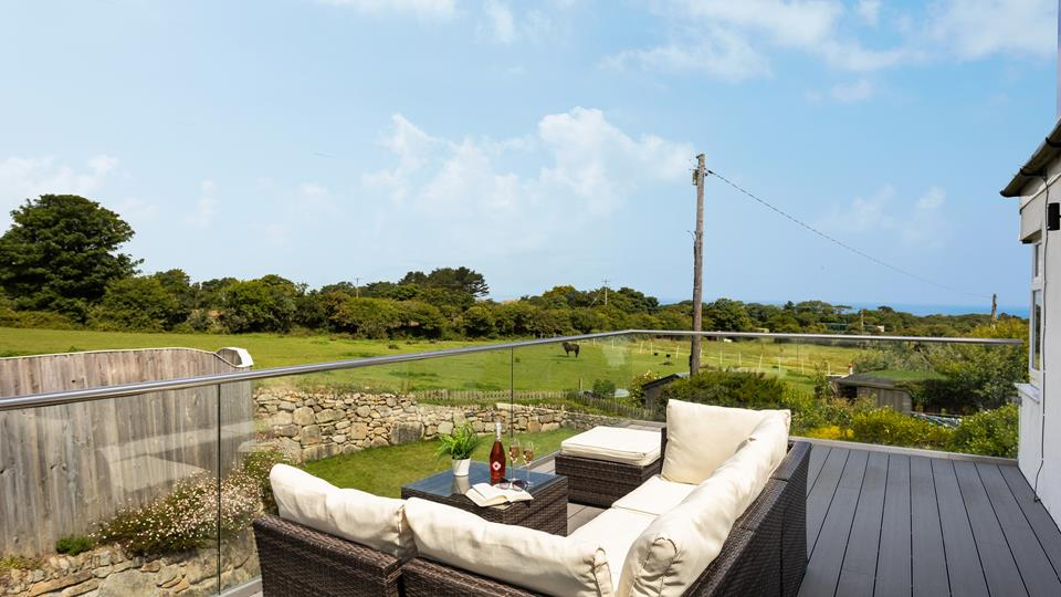 Relax on the large balcony, glass of wine in hand, overlooking the meadows and distant sea views.