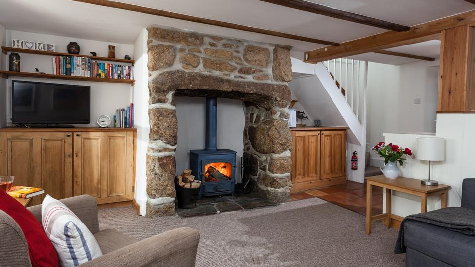 An exposed stone inglenook fireplace with woodburner creates a very cosy atmosphere for this sitting room.