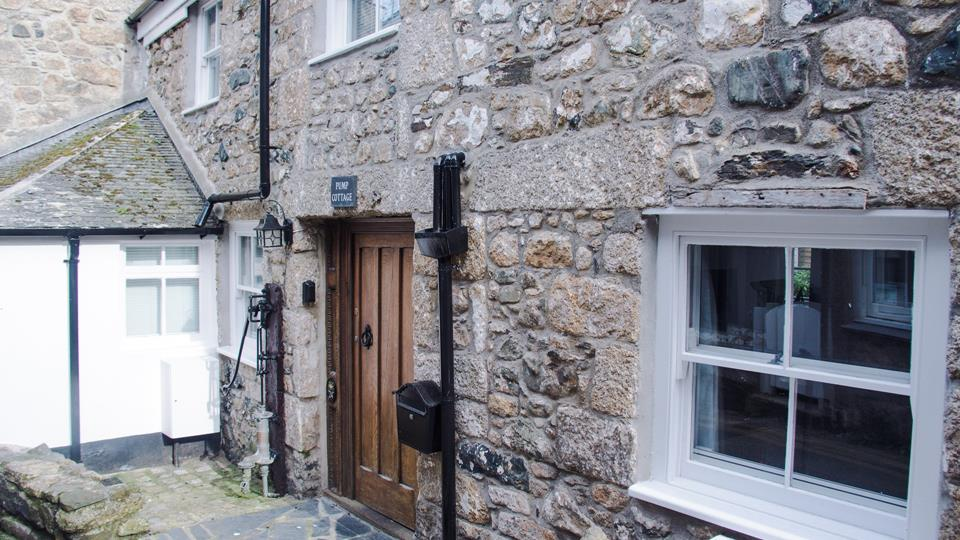 Pump Cottage has a granite stone-face facade with original cast iron water pump and a solid oak entrance door.
