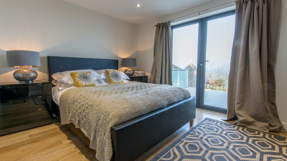 Bedroom one has a leather bedstead king size bed with high-shine bedside chests and hammered metal side lamps.