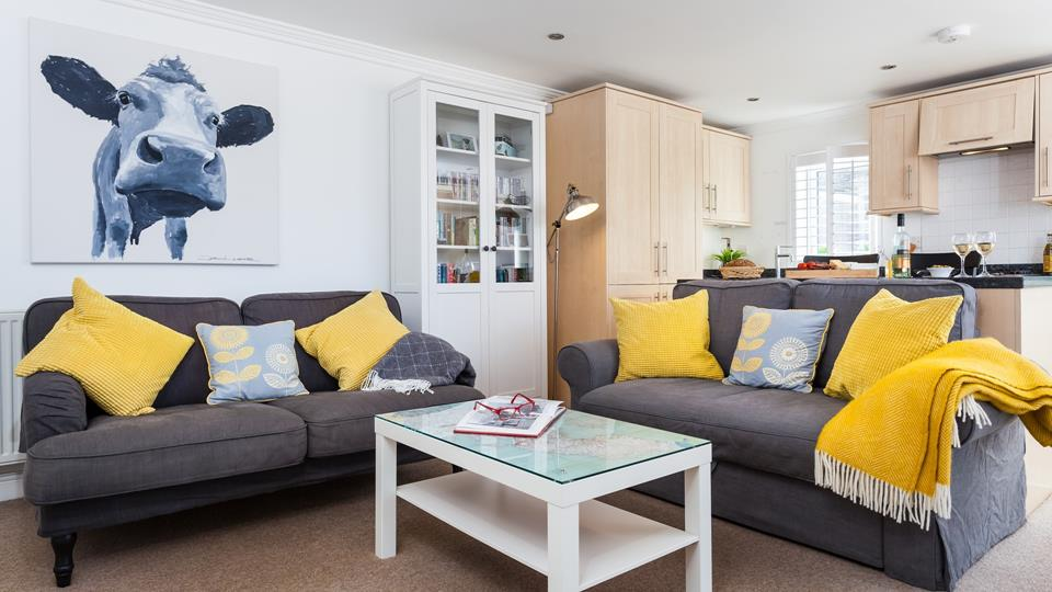 The living space has two textile-covered sofas with zingy accent cushions and woven tasselled throws.