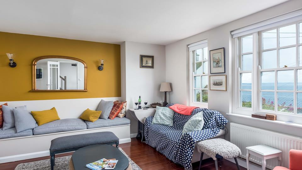 A bright and colourful sitting room with large windows with sea views.