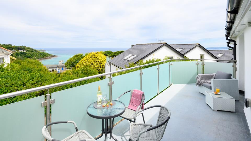 The private stainless steel and aqua glass balcony has a lovely sea view across Carbis bay.