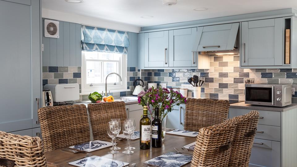 The kitchen has soft blue painted wood cupboards and Corian grey worktops and contrasting ceramic wall tiles.