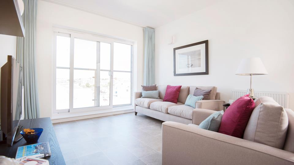 The living room is decorated in fresh, fun tones with the glass balcony doors providing plenty of natural light.