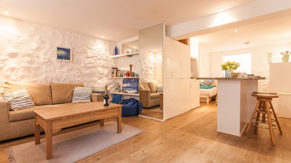 The living space is laid out in an open-plan fashion with natural oak wood flooring throughout.