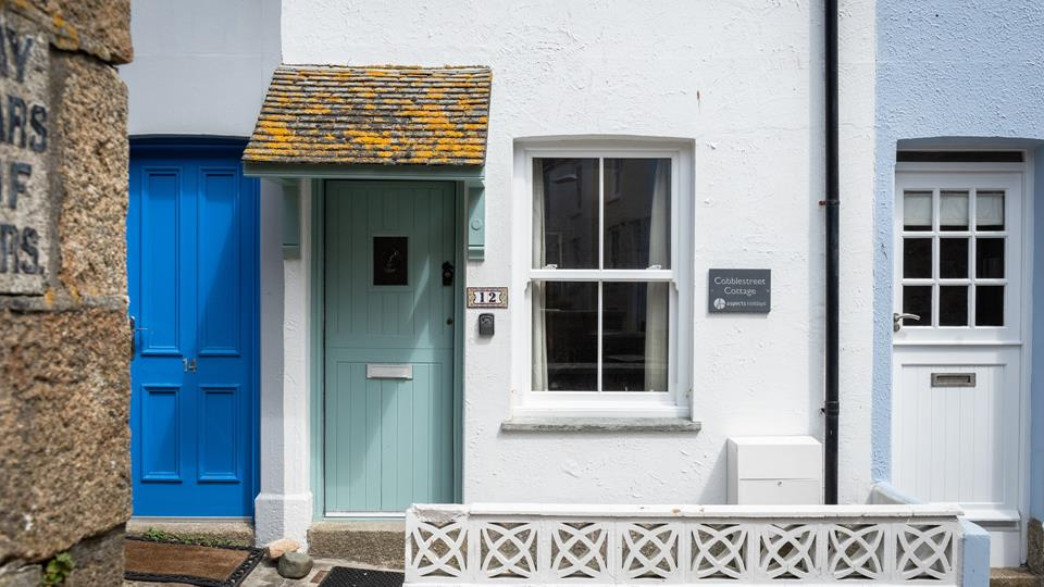 The original granite step leading from the cobbled street to the cottage entrance door has a slate tiled traditional canopy.