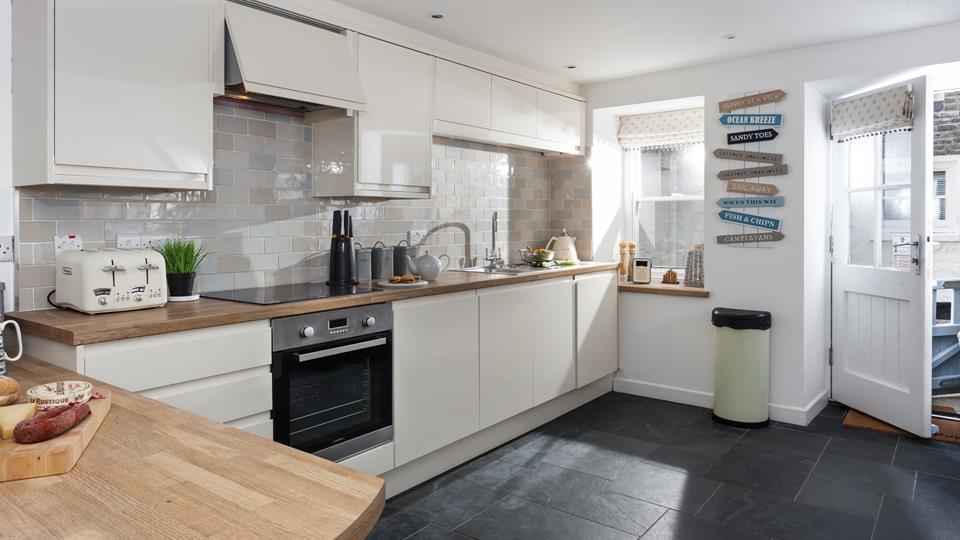 The kitchen is beautifully decorated in neutral tones and is fabulously well-equipped with modern appliances.