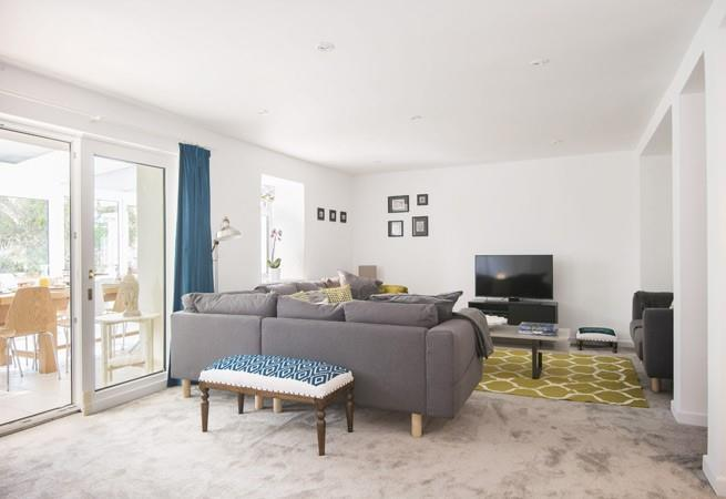 Sitting room with corner sofa, TV/DVD, music system and doors to the conservatory.