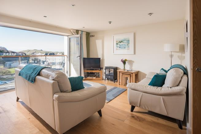 With the Bi-fold doors open out onto the balcony, the open plan living area is filled with light.