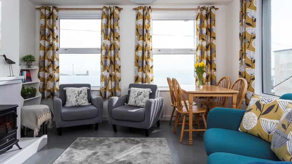 The Sitting and dining room has contemporary furniture and tasteful use of colours, accent cushions on the teal sofa match the eyelet curtains.