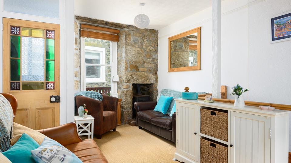 The sitting room has two leather sofas and a bucket style leather armchair, the exposed stone-faced wall with feature fireplace adds plenty of character.