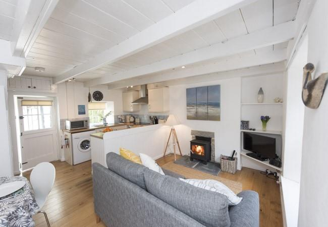 The cosy living/dining/kitchen area is enhanced with a woodburning stove