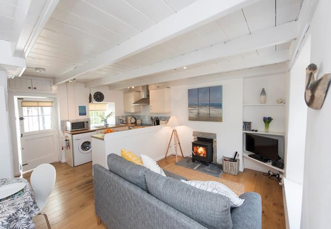 The cosy living/dining/kitchen area is enhanced with a woodburning stove.