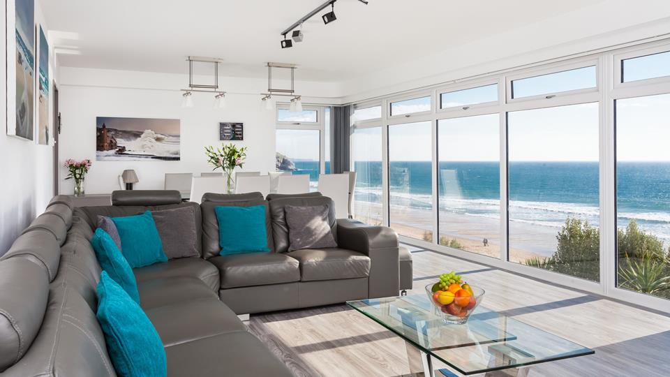 The seaside sitting room has a comfy eight seater sofa and a stylish glass coffee table.