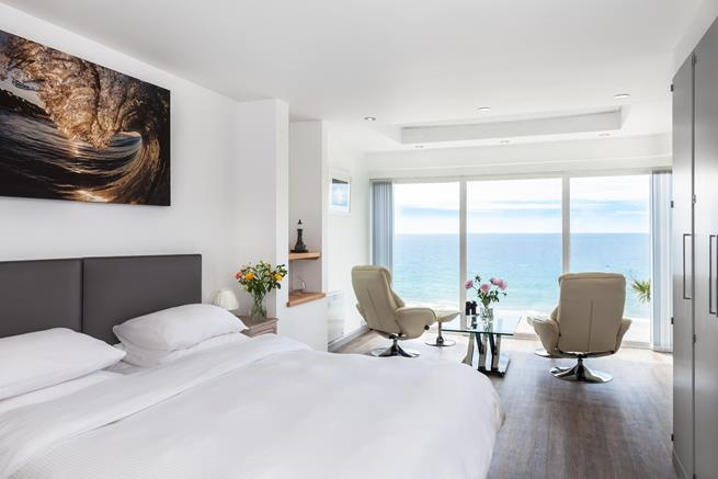 Bedroom 1 has a comfy king size bed, plus two gorgeous arm chairs looking out over the ocean.