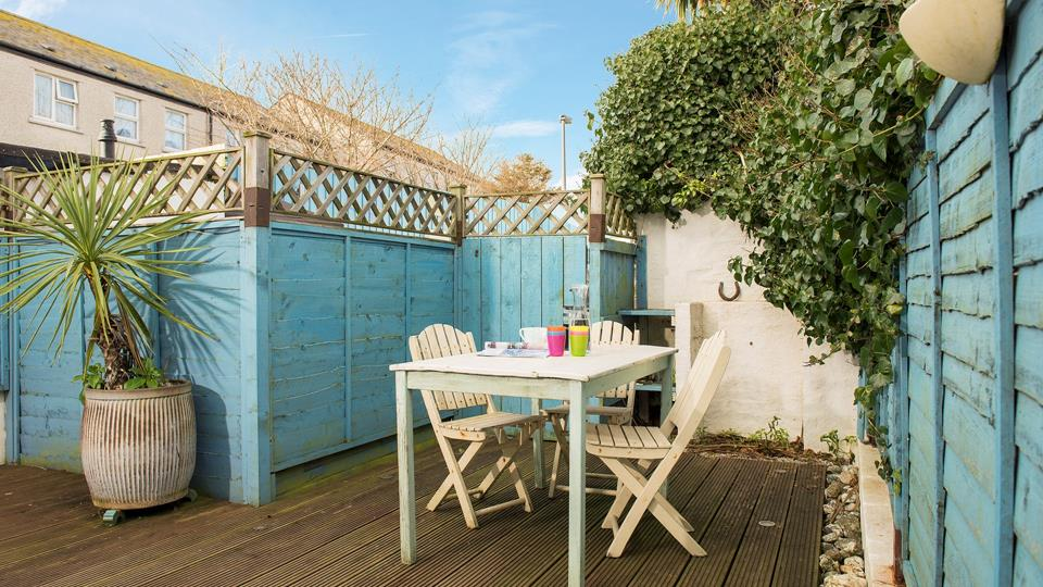 The enclosed garden with decking and faux turf is a great spot for some lunch outdoors.