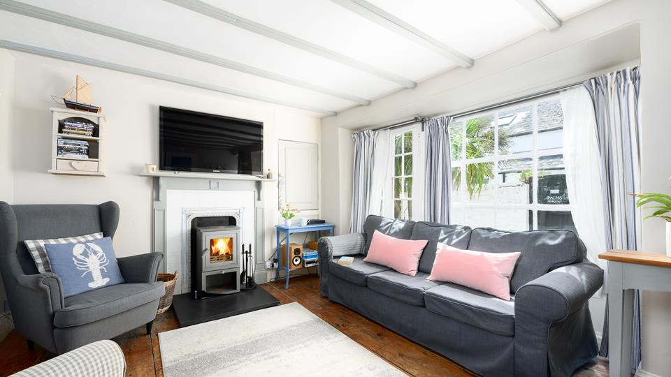 The quaint sitting room with a roaring woodburner for the colder months, completes the cosy feel of this traditional Cornish cottage.