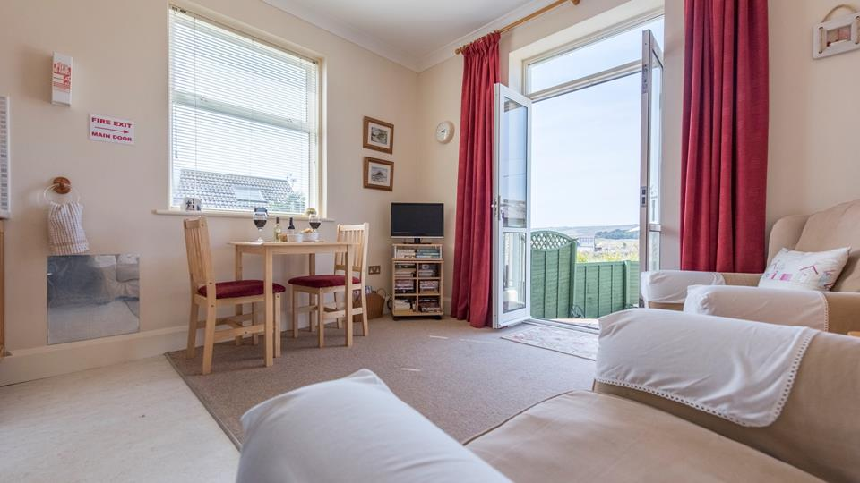 Enter through the double doors into the living area - this property has stunning views across Marazion.