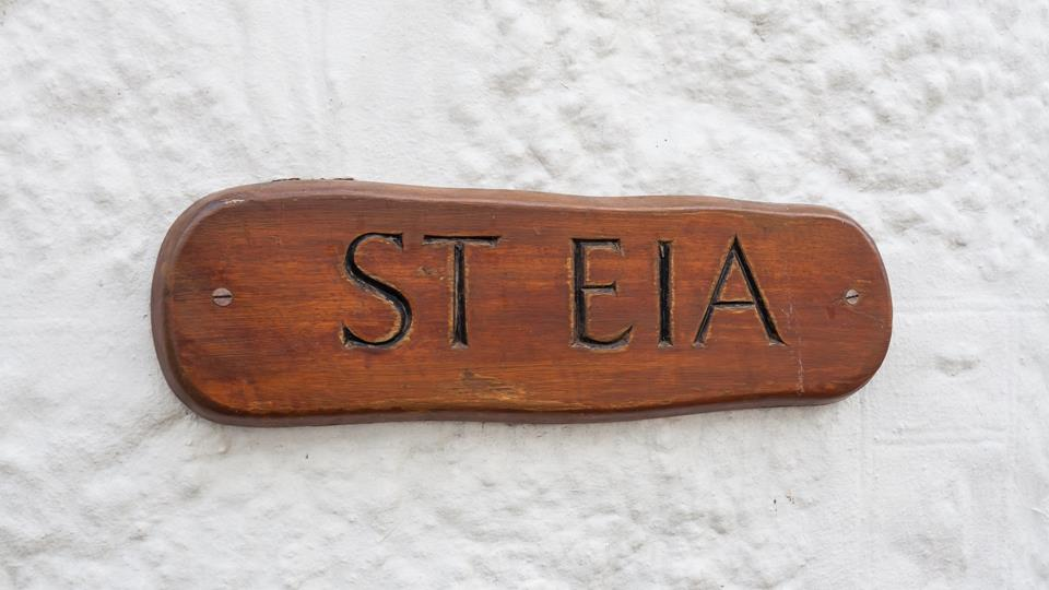 The cottage has a traditional whitewashed exterior and the wooden property sign looks great.