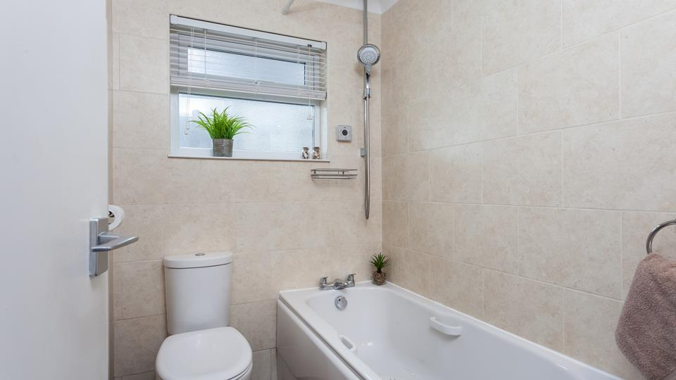 The bathroom has a bath with a shower over.