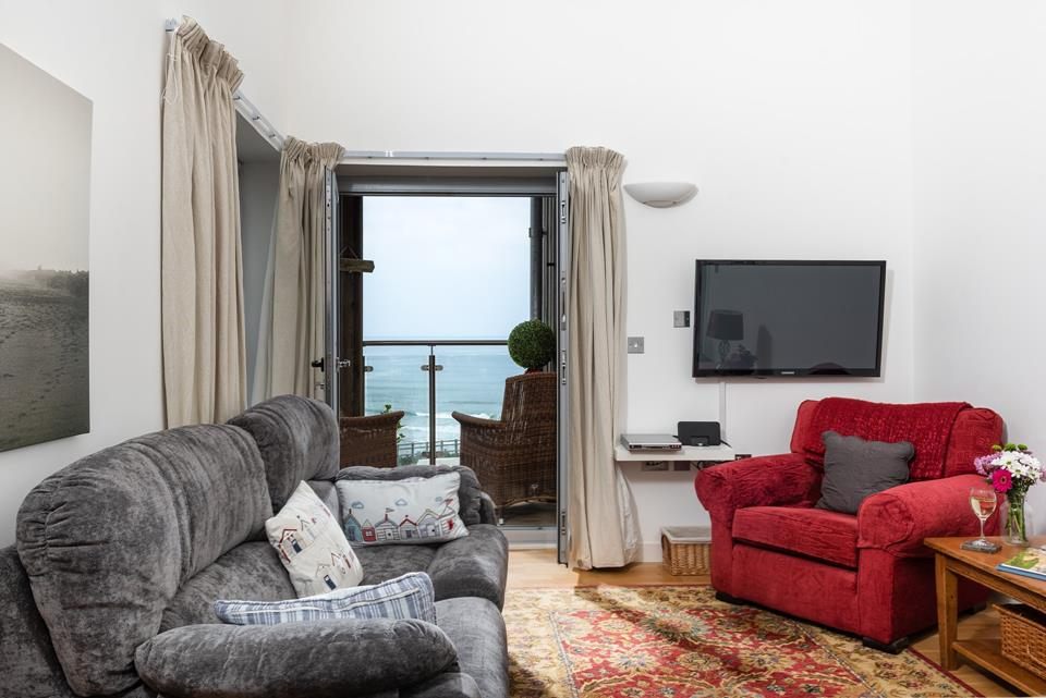 The comfortable sitting area is great for relaxing of an evening, with the balcony doors open to let in the fresh sea air.