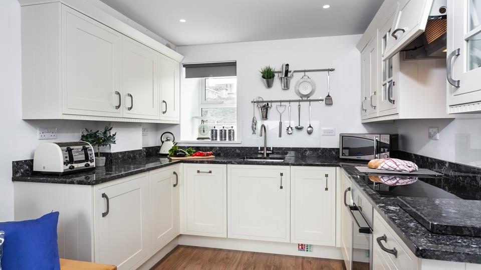This well-equipped kitchen with modern appliances is sure to delight any budding chef.