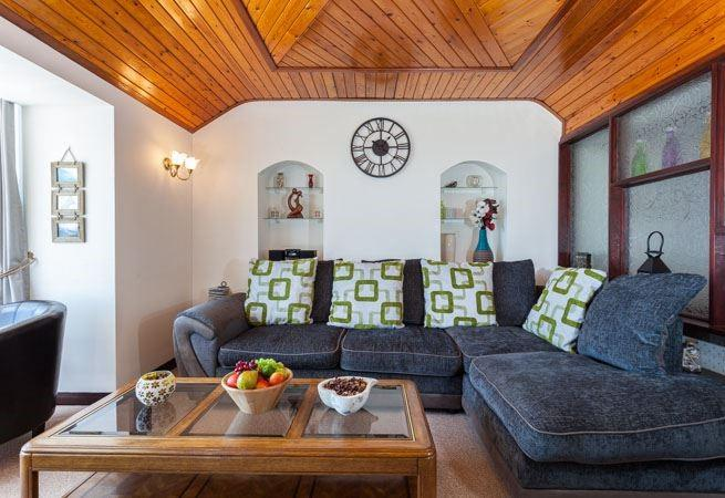 The sitting room has a large L-shaped sofa, two tub chairs, a TV and stunning sea views
