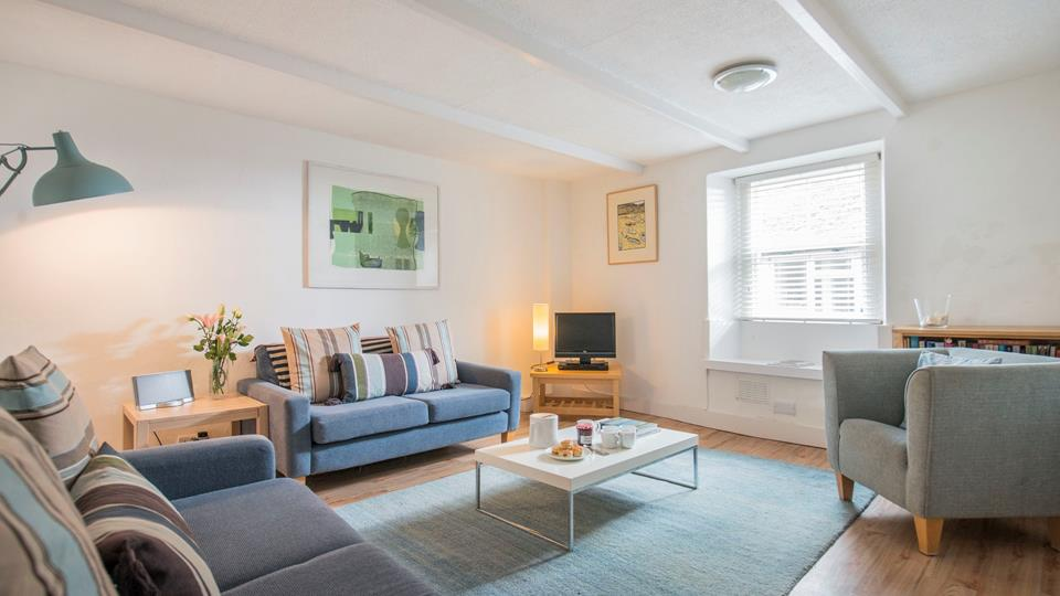 The sitting room has a modern and homely feel, painted exposed beams give the room great character which works well against the contemporary furniture.