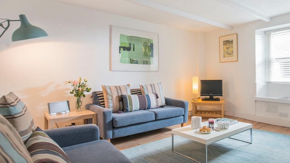 The sitting room has a modern and homely feel, perfect for snuggling up to watch a movie or get lost in a book.
