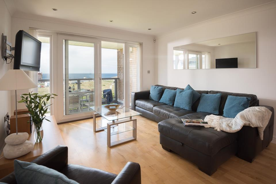 The open plan living area with doors to the balcony and looking out onto the headland beyond.