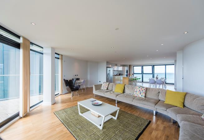 The light open plan living space with doors to the balcony.