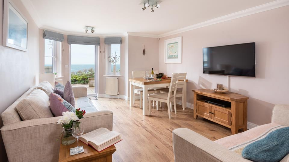 The open plan living area is the perfect place to relax and unwind, whether you're taking in the sea views or catching up with a glass of wine.