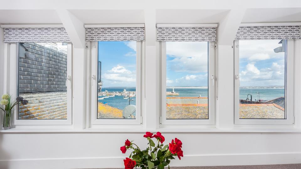 The sitting room has a stunning view over rooftops down to St Ives Harbour with Godrevy Lighthouse in the distance.