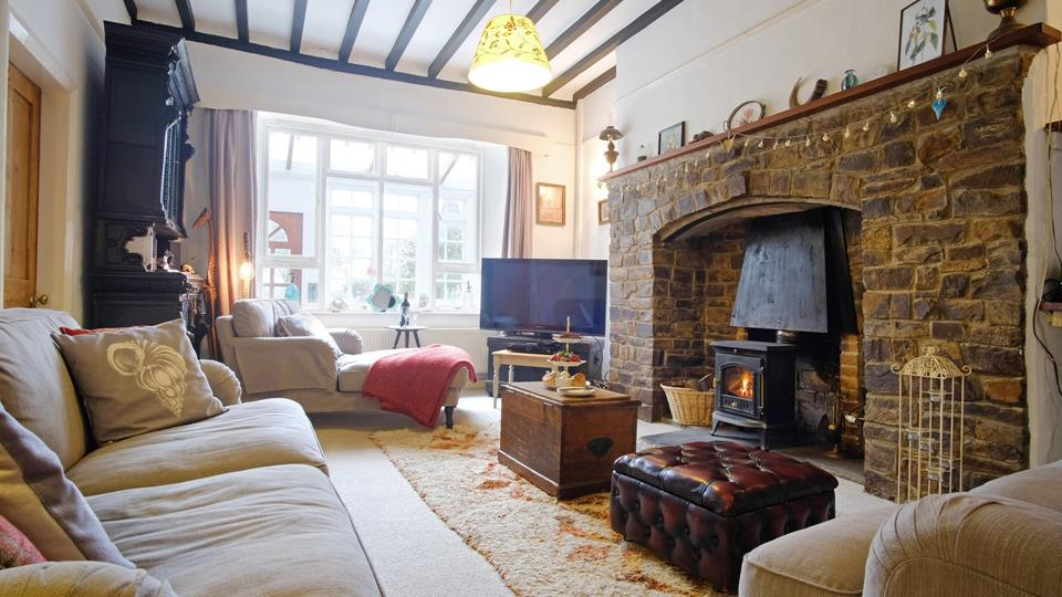 The grand fireplace is the centrepiece of this cosy living room which overlooks the pretty garden and sunroom.