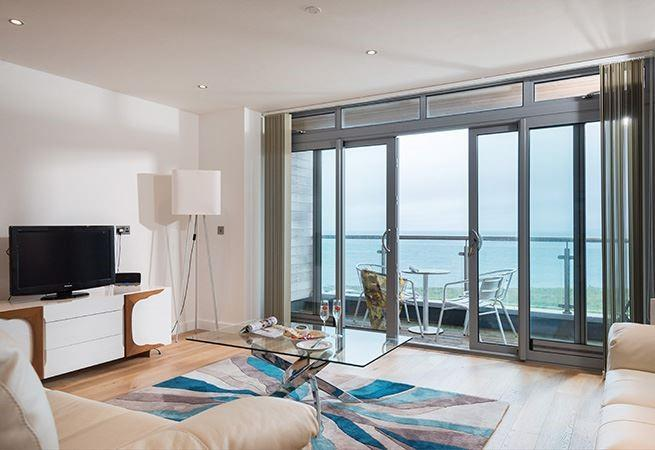 Open plan sitting area with sea views and doors to balcony.