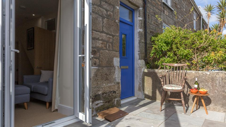 The blue front door of this gorgeous cottage leads onto the small private patio area.