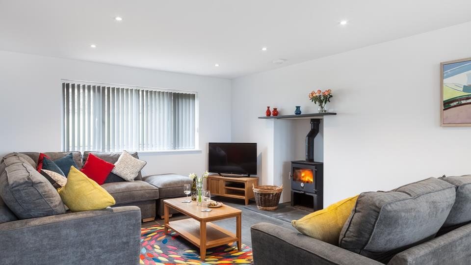The family sitting room complete with a TV and woodburner makes this house really feel like home.