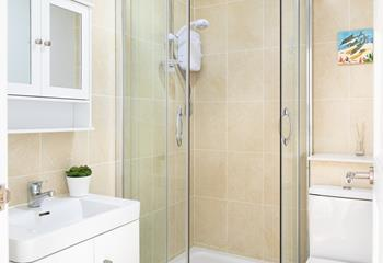 The bathroom matches the bedrooms calming pastel hues and has a shower, with WC and basin.
