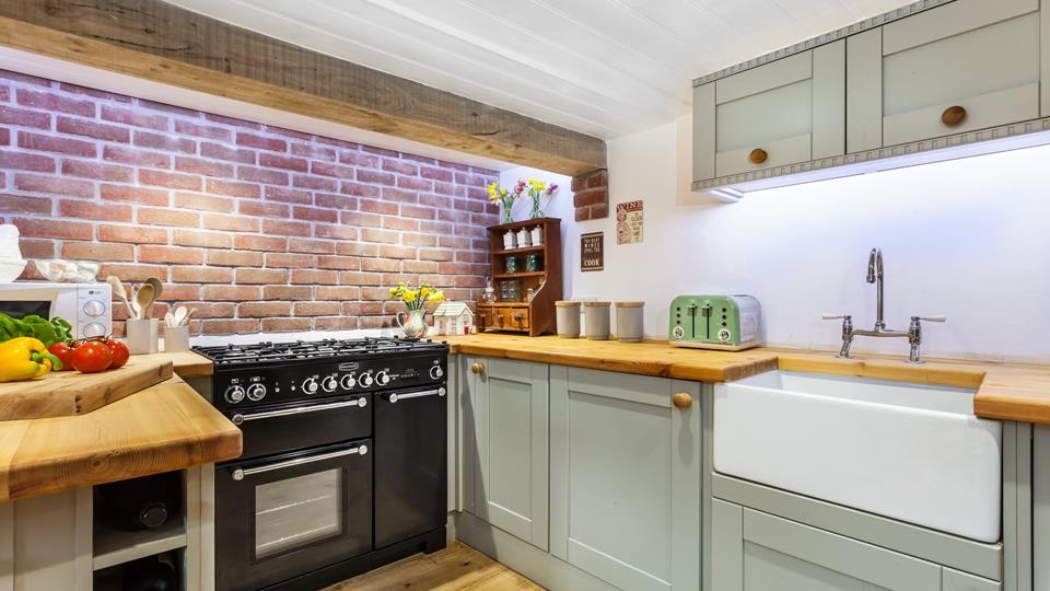 An exposed brick wall and exposed wooden beams add lots of character to this kitchen.