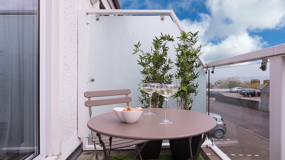 The private balcony has a taupe painted metal bistro table and chairs.