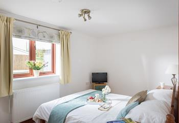 The comfortable double bedroom looks out onto the garden and has both blinds and curtains, allowing for a more restful nights sleep.