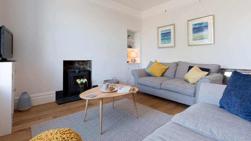 Cosy down in the homely living area where soft tones and seaside art will help you to step out of city life and unwind.