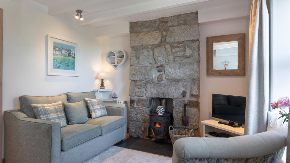 The exposed stone feature wall adds character to this room.